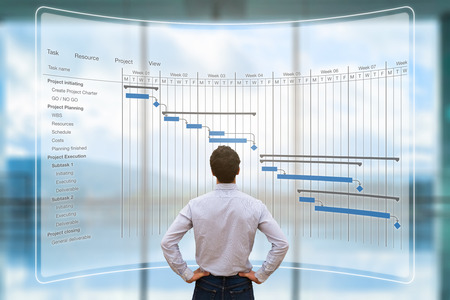 Project manager looking at AR screen with Gantt chart schedule or planning showing tasks and deadlines Foto de archivo