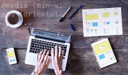 Webdesigner schetsende responsieve website wireframe mockup met laptop, smartphone en digitale tablet computer op houten tafel, UI en UX front end development concept, bovenaanzicht Stockfoto - 87166593