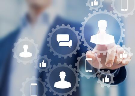 Concept de marketing numérique des médias sociaux avec des icônes de profil de personnes, comme, commentaire et smartphone à l'intérieur du réseau d'engrenages connectés, homme d'affaires en arrière-plan Banque d'images