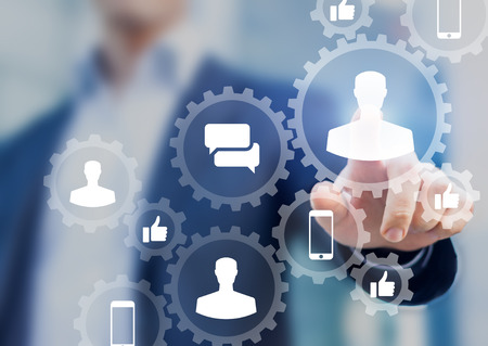 Social media digital marketing concept with icons of people profile, like, comment and smartphone inside connected gears network, businessman in background