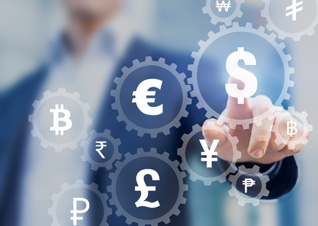 Foreign exchange trading concept with currency symbols inside connected gears to show connection between money, businessman in background Stock Photo