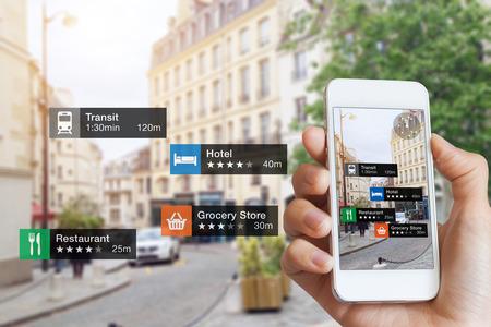 Tecnología de información de realidad aumentada (AR) sobre negocios y servicios cercanos en la guía de pantalla del teléfono inteligente cliente o turista en la ciudad, primer plano de la mano sosteniendo teléfono móvil, calle borrosa