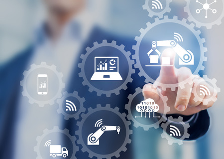 Smart factory and industry 4.0 concept with connected production robots exchanging data with internet of things (IoT) and cloud computing technology, businessman touching interface with icons in gears Imagens