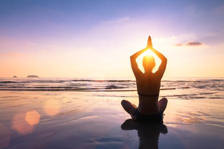 Yoga et méditation sur la plage calme et paisible au coucher du soleil, en forme de jeune femme Banque d'images