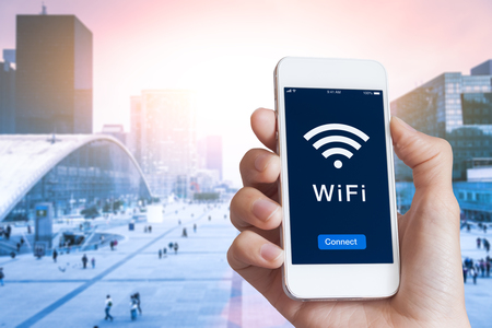 Business person connecting to WiFi hotspot on smartphone screen in financial district to access wireless internet with blurred cityscape in background