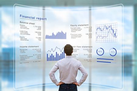 Przedsiębiorca analizujący dane z raportów finansowych z działalności firmy (bilans, rachunek zysków i strat) na wirtualnym ekranie komputera z wykresami biznesowymi, fintech