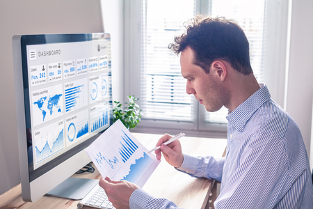 Digital marketing analytics technology with metrics and key performance indicators dashboard on computer screen, person analyzing data chart and advertisement campaign strategy in office