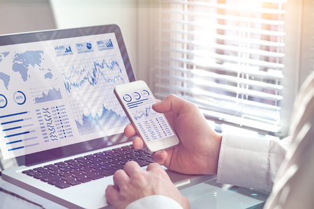 Business analytics dashboard technology on computer and smartphone screen with key performance indicator (KPI) about financial operations statistics and return on investment, office worker Standard-Bild