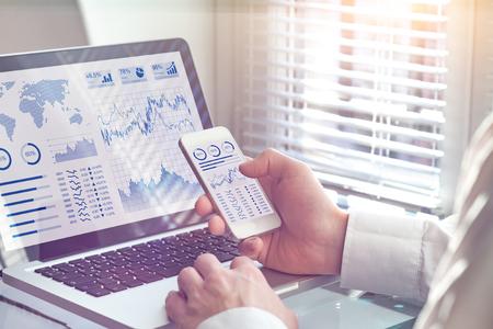 Dashboardtechnologie voor bedrijfsanalyses op computer- en smartphonescherm met key performance indicator (KPI) over statistieken van financiële operaties en rendement op investering, kantoormedewerker