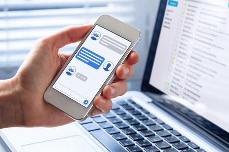 Chatbot-Konversation auf der Smartphone-Bildschirm-App-Oberfläche mit Technologie für künstliche Intelligenz, die Kundenunterstützung und Informationen für virtuelle Assistenten bereitstellt, Person Hand hält Handy