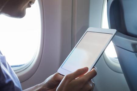 Passagier, der während des Fluges einen Tablet-Computer in der Flugzeugkabine mit drahtlosem Internet verwendet, um E-Mails oder ein E-Book zu lesen, Hände halten Gerät mit weißem leerem Bildschirm für Kopienraum, Unterhaltung an Bord Standard-Bild