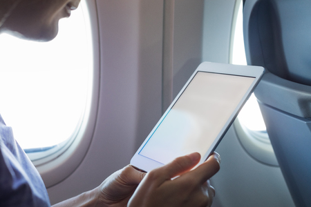 Passenger using tablet computer in airplane cabin during flight with wireless internet to read emails or an ebook, hands holding device with white empty screen for copy-space, onboard entertainment