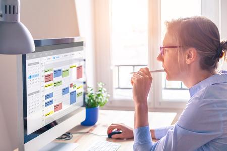 Person, die Kalender auf dem Computer verwendet, um das Zeitmanagement zu verbessern, Termine, Ereignisse, Aufgaben und Besprechungen effizient zu planen, die Produktivität zu verbessern, Wochentag und Arbeitszeiten zu organisieren, Geschäftsfrau, Büro