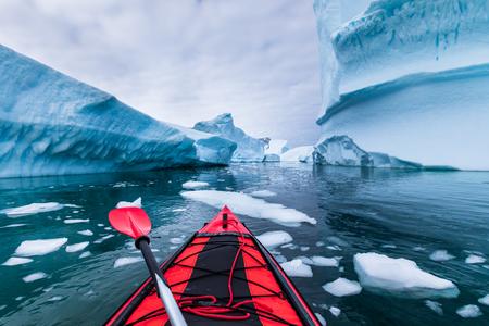 Kajakfahren in der Antarktis zwischen Eisbergen mit aufblasbarem Kajak, extremes Abenteuer auf der antarktischen Halbinsel, wunderschöne unberührte Landschaft, Meerwasserpaddelaktivität