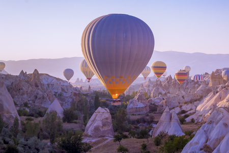 Hot air balloons flying in beautiful Cappadocia hilly landscape, amazing tourism attraction in Goreme, Anatolia, Turkey, morning sun light
