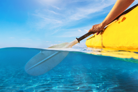 Split view of person kayaking in transparent blue sea, underwater and above water photography of kayak and paddle in warm summer tropical travel destination for vacation holidays