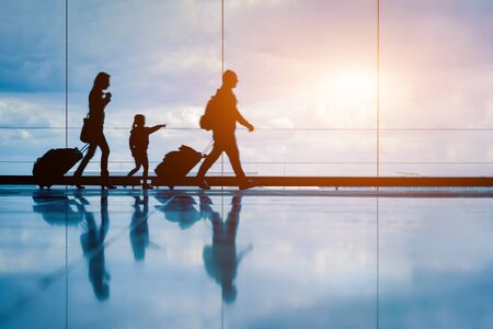 Family at airport travelling with young child and luggage walking to departure gate, girl pointing at airplanes through window, silhouette of people, abstract international air travel concept Imagens