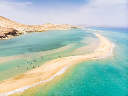 Aerial view of beach in Fuerteventura island with windsurfers learning windsurfing in blue turquoise water during summer vacation holidays, Canary islands from drone