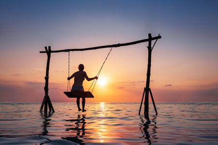 Ragazza felice che si rilassa sulla spiaggia sull'oscillazione della corda sopra l'acqua di mare al tramonto, località di soggiorno di vacanze estive