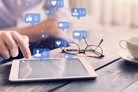 Koncepcja interakcji sieci społecznościowych z ikonami komentarzy, prośbami o kontakt od znajomych i wiadomościami pokazującymi zaangażowanie użytkowników i marketing cyfrowy na urządzeniach mobilnych, osoba dotykająca ekranu Zdjęcie Seryjne