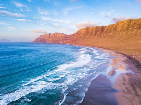 Famara Atlantic ocean beach surf spot aerial view  of scenic landscape from drone in Lanzarote, Canary islands during warm sunny summer day, vacation holidays destination for surfing near La Santa