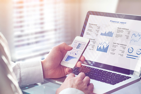 Accountant working on consolidated financial report of corporate operations, consultant auditing finance data (balance sheet, income statement) on screen with business charts, fintech, manager Banco de Imagens