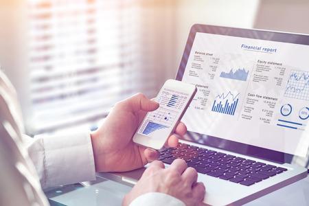 Comptable travaillant sur le rapport financier consolidé des opérations de l'entreprise, consultant vérifiant les données financières (bilan, compte de résultat) à l'écran avec des graphiques commerciaux, fintech, gestionnaire Banque d'images