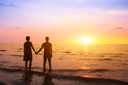 Couple romantique sur la plage au coucher du soleil en regardant l'horizon, vacances de lune de miel à destination de la mer, silhouette de deux amoureux se tenant la main