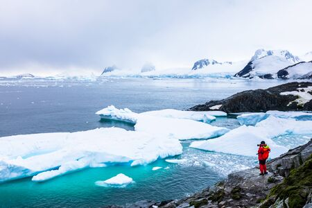 Tourist taking photos of amazing frozen landscape in Antarctica with icebergs, snow, mountains and glaciers, beautiful nature in Antarctic Peninsula with ice 스톡 콘텐츠