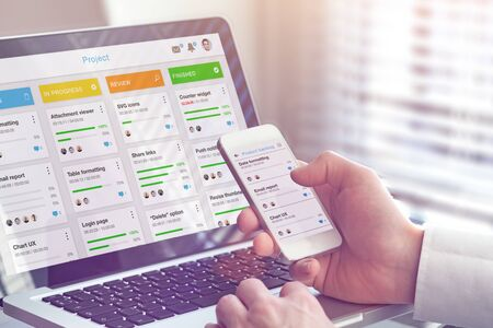 Manager working with agile framework board for lean product development such as scrum or kanban methodology, project management with iterative or incremental strategy, smartphone and laptop in office Stock Photo