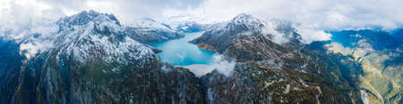 Panorama of arch dam and reservoir lake in snow covered Swiss Alps mountains to produce renewable energy from hydropower, sustainable hydroelectricity, aerial drone view, cold autumn weather