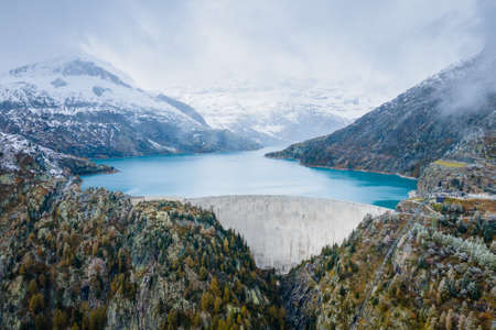 Hydropower generated from arch dam and reservoir lake in snow covered Swiss Alps mountains to produce renewable energy, sustainable hydroelectricity, aerial drone view, cold autumn weather Reklamní fotografie