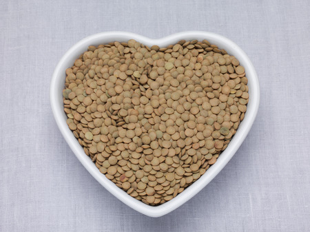Raw Le Puy green lentils in a heart shaped bowl on a woven table cloth photo