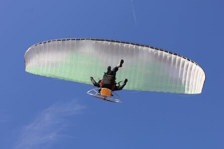 engine powered: a paraglider flying seen from below Stock Photo