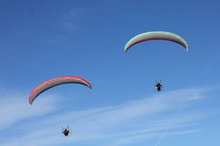 two flying paragliders in the sky photo