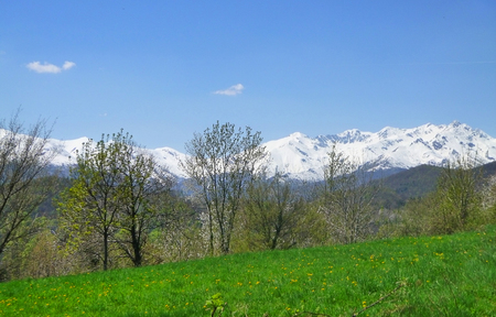 a landscape with meadows and mountains in spring