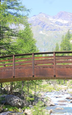 a bridge on the river in front of mountains Standard-Bild - 127530708