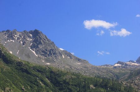 a panorama with mountains, rocks, clouds and vegetation Standard-Bild - 127530862