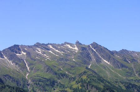 a panorama of a mountain range with glacier, vegetation and rocks Standard-Bild - 127530873