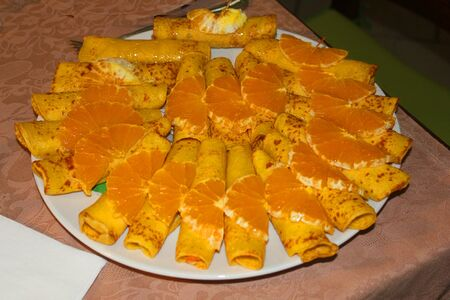 a dish with crepes with orange slices