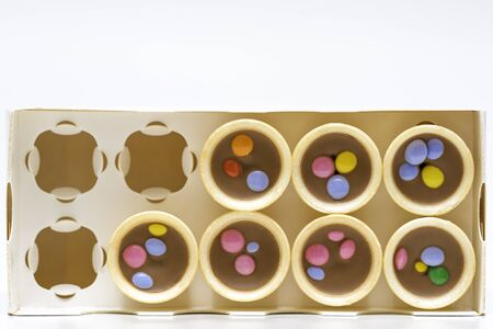 Ice cream cones with chocolate decorated with candy, on white background