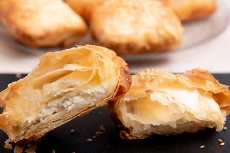 white cheese puff pastry on a black plate and a white plate
