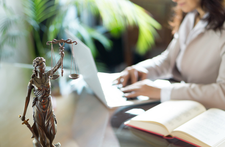Lawyer office. Statue of Justice with scales and lawyer working on a laptop. Legal law, advice and justice concept Archivio Fotografico