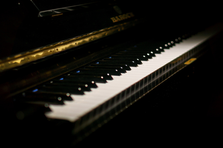 Close up of piano keys of a classic piano in the dark