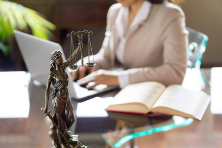 Lawyer office. Statue of Justice with scales and lawyer working on a laptop. Legal law, advice and justice concept Imagens