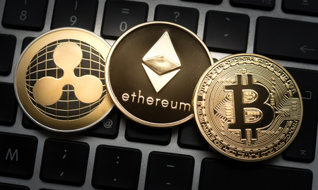 Cryptocurrencies Ethereum, Ripple, and Bitcoin coins on computer laptop keyboard. Finance, investment and money concept