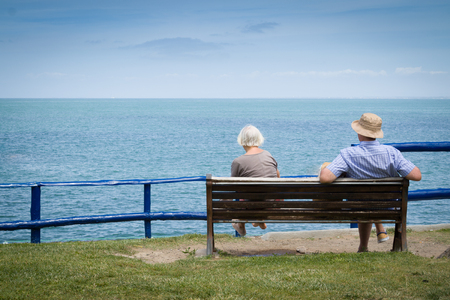Elderly couple relaxing in front of the sea view. With copyspace above. Stock Photo