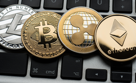 Cryptocurrencies Ethereum, Ripple, Bitcoin and Litecoin coins on computer laptop keyboard. Finance, investment and money concept