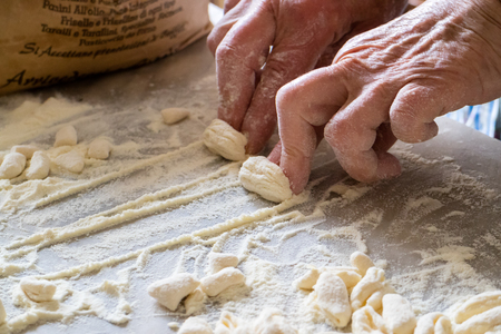 Hands of Italian woman making traditional fresh homemade pasta on a marble table