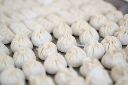 Raw Chinese dumplings on table, closeup, selected focus. Dumplings are among the most typical food in China and Asia